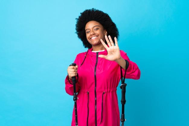 Jovem africano americano com mochila e bastões de trekking isolados na parede azul, contando cinco com os dedos