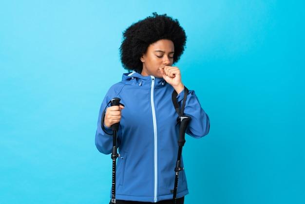 Jovem africano americano com mochila e bastões de trekking isolados na parede azul, tossindo muito
