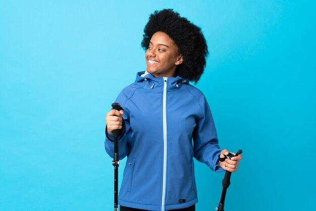 Jovem africano americano com mochila e pólos de trekking isolados na parede azul, olhando para o lado e sorrindo