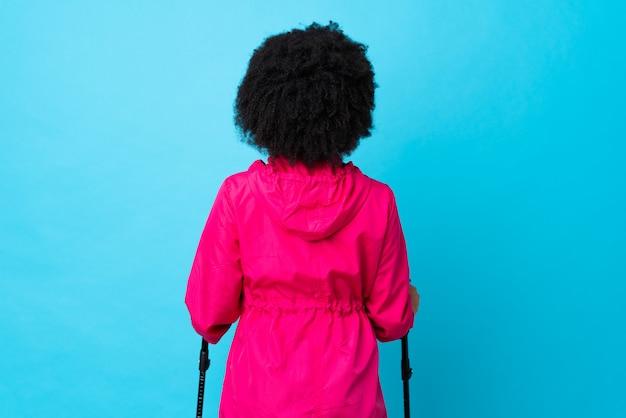 Jovem africano americano com mochila e pólos de trekking isolados no azul em posição traseira