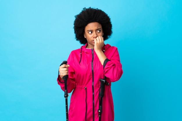 Jovem africano americano com mochila e pólos de trekking isolados no azul nervoso e assustado, colocando as mãos na boca