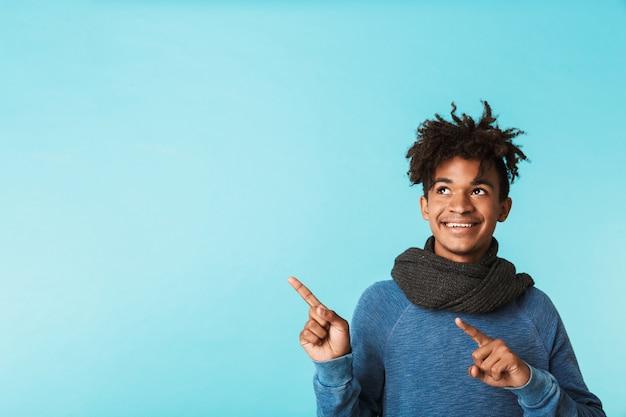 Jovem africano animado usando lenço de inverno em pé isolado sobre o azul, apontando para o espaço da cópia