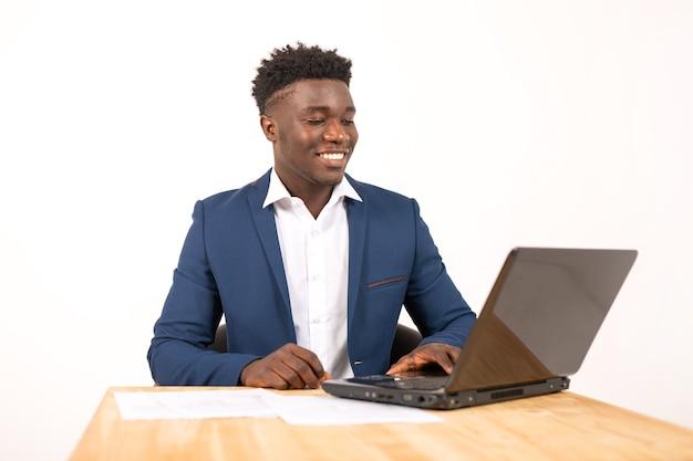 Jovem africano bonito à mesa com o laptop