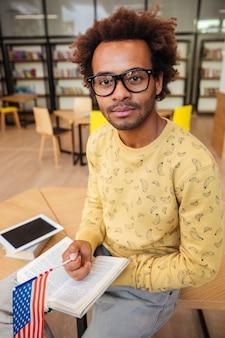 Jovem africano bonito com bandeira americana lendo livro na biblioteca