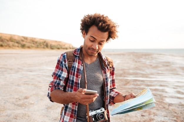 Jovem africano bonito com mapa e foto vintage usando telefone celular ao ar livre