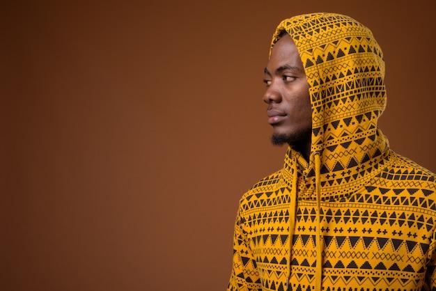 Jovem africano bonito contra o fundo marrom