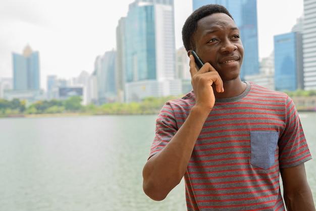 Jovem africano bonito falando ao telefone no parque