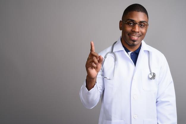 Jovem africano bonito médico em cinza
