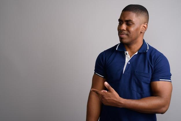 Jovem africano bonito vestindo uma camisa pólo azul cinza
