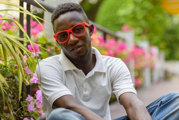 Jovem africano com óculos sentado no parque ao ar livre