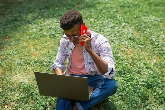 Jovem africano com telefone celular e laptop