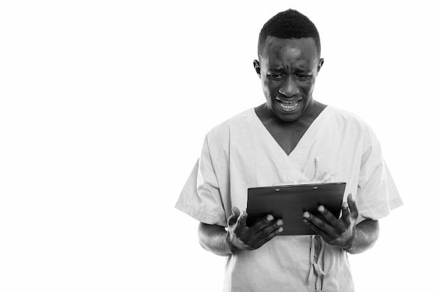 Jovem africano como paciente de hospital isolado contra uma parede branca em preto e branco
