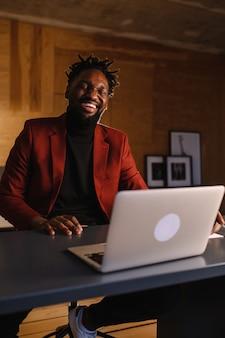 Jovem africano confiante olhando para uma videoconferência por webcam, no escritório, feliz empresário mestiço falando, fazendo uma entrevista de emprego por vídeo chat online, sente-se na mesa