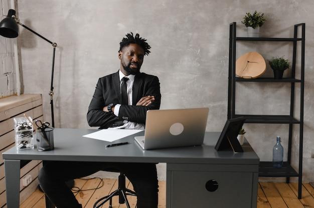 Jovem africano confiante olhando para videoconferência com webcam no escritório