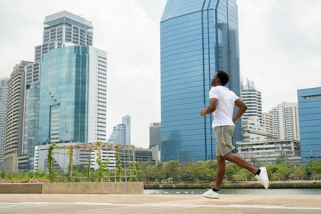 Jovem africano correndo ao ar livre no parque com a paisagem urbana