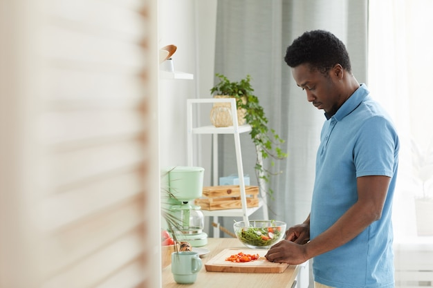 Jovem africano cortando legumes na tábua, ele cozinhando salada de legumes na cozinha
