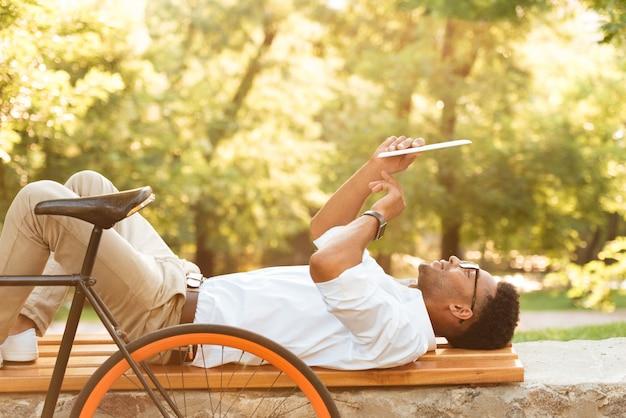 Jovem africano de manhã cedo com bicicleta ao ar livre usando tablet