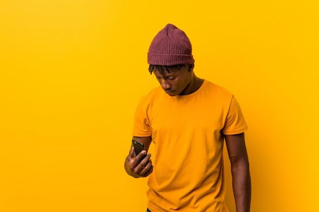 Jovem africano de pé contra um fundo amarelo, usando um chapéu e usando um telefone