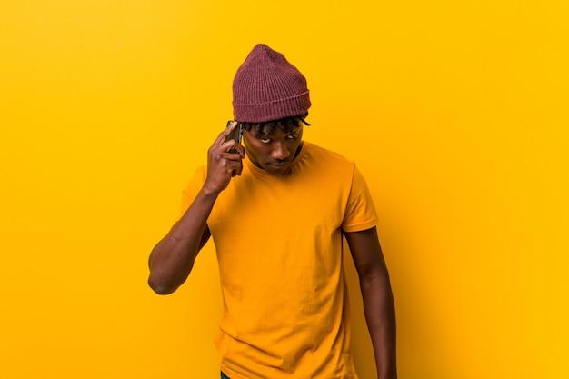 Jovem africano de pé contra um fundo amarelo, vestindo um chapéu e usando um telefone