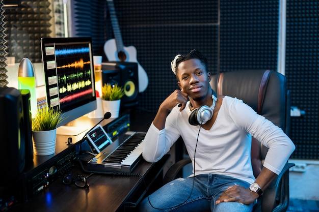 Jovem africano de sucesso em trajes casuais sentado perto do local de trabalho com o monitor do computador no estúdio de gravação de som