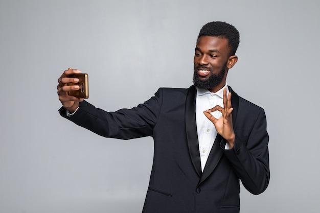 Jovem africano de terno tirando uma selfie com um gesto de aprovação
