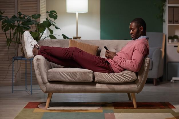 Jovem africano descansando no sofá com o celular durante suas horas de lazer