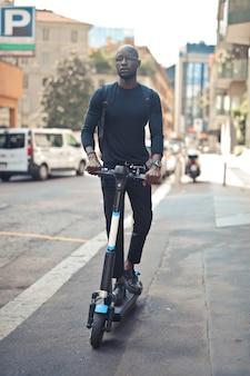 Jovem africano elegante com óculos, andando de scooter sob o sol durante o dia