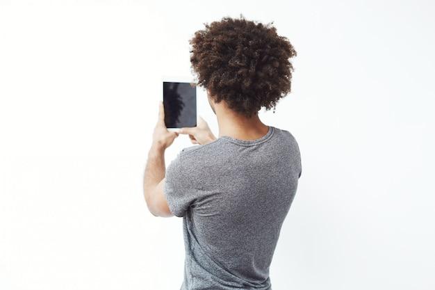 Jovem africano em pé de volta para a câmera, olhando para o tablet.