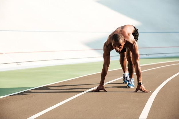 Jovem africano esportes homem na posição inicial, pronto para começar