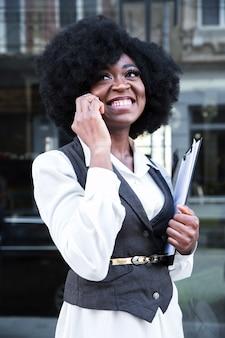 Jovem, africano, executiva, falando telefone móvel, segurando clipboard, em, mão