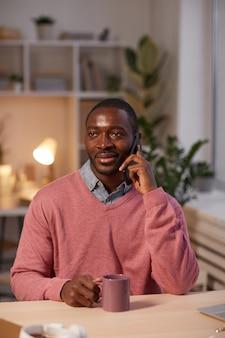 Jovem africano falando no celular enquanto está sentado à mesa no escritório tomando café