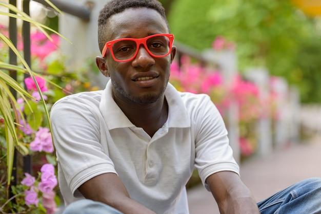 Jovem africano feliz com óculos, sorrindo e sentado ao ar livre no parque
