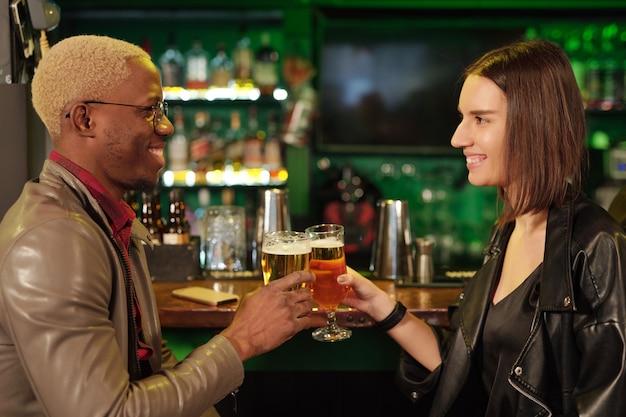 Jovem africano feliz em trajes casuais elegantes, olhando para a namorada com um sorriso, enquanto tilintava copos de cerveja na frente da câmera no bar