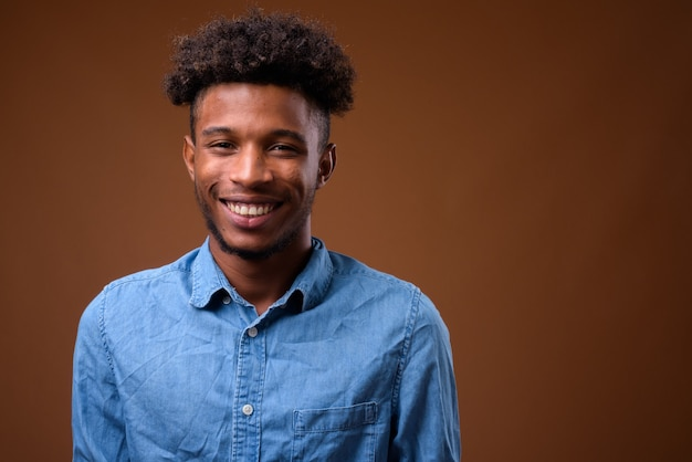 Jovem africano feliz sorrindo em marrom