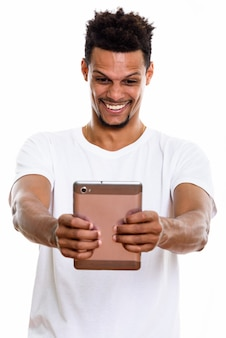 Jovem africano feliz sorrindo enquanto segura um tablet digital