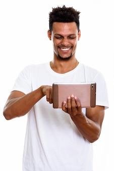 Jovem africano feliz sorrindo enquanto usa tablet digital