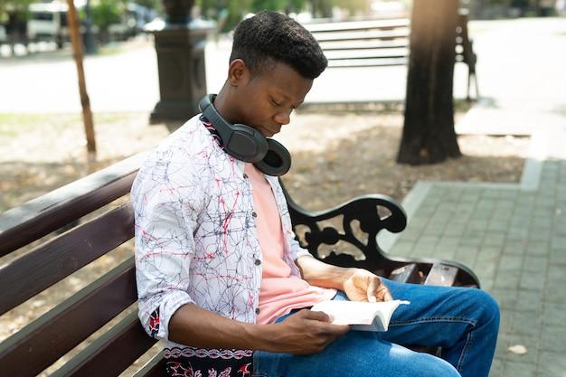 Jovem africano lendo um livro no parque