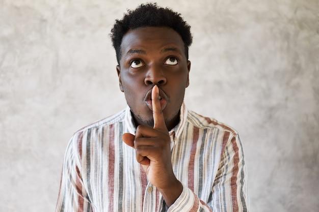 Jovem africano misterioso olhando para cima, segurando o dedo da frente nos lábios