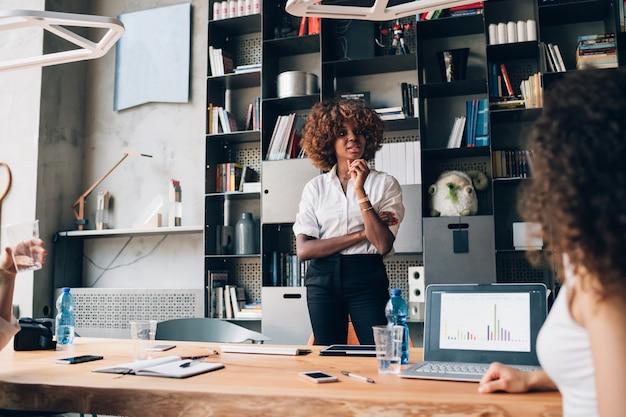 Jovem, africano, mulher negócios fica, em, co-working, escritório, e, trabalhando, ligado, projeto