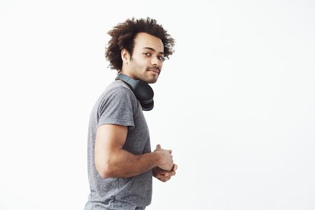 Jovem africano, olhando com desconfiança para a câmera em pé na parede de perfil branco com seu pescoço de fones de ouvido sem fio.