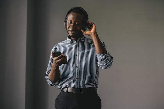 Jovem africano ouvindo música com fones de ouvido sem fio e dançando em casa