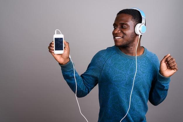 Jovem africano ouvindo música em cinza