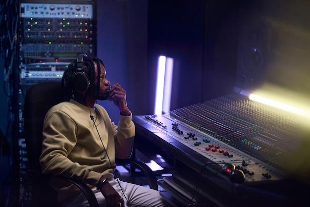 Jovem africano ouvindo música em fones de ouvido, sentado ao teclado de música no estúdio