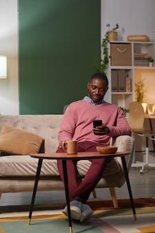 Jovem africano sentado no sofá em frente à mesa com uma xícara de café e usando seu telefone celular durante a pausa para o café