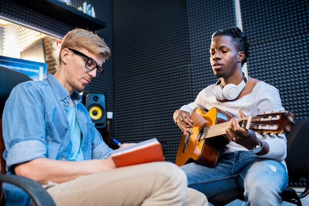 Jovem africano tocando violão e cantando enquanto seu colega faz anotações no bloco de notas em uma reunião de trabalho no estúdio