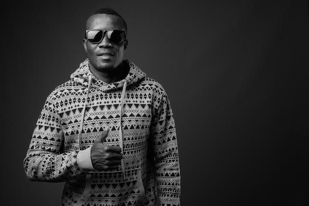 Jovem africano usando capuz e óculos escuros contra a parede cinza. preto e branco