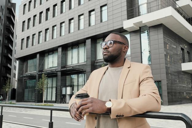 Jovem africano usando óculos, bebendo café ao ar livre, apreciando a vista da cidade