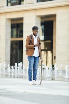 Jovem africano usando smartphone na cidade