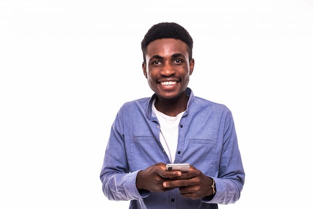 Jovem africano usando telefone celular isolado contra parede branca