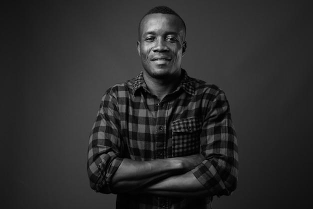 Jovem africano vestindo camisa quadriculada contra a parede cinza. preto e branco